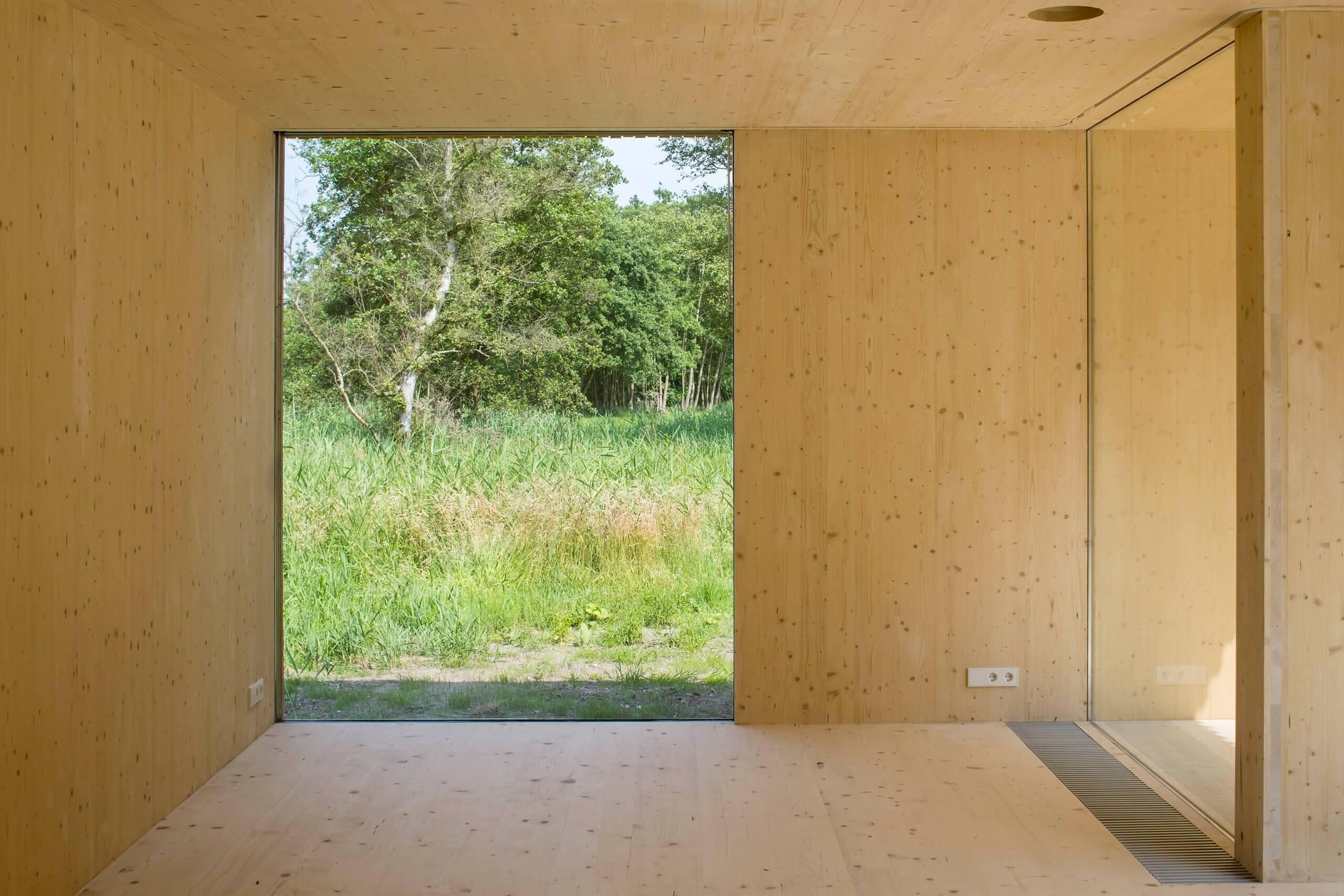 De vloeren, wanden en het dak van de uitbreiding zijn volledig van massief hout, dat aan de binnenzijde onafgewerkt in het zicht is gebleven.
